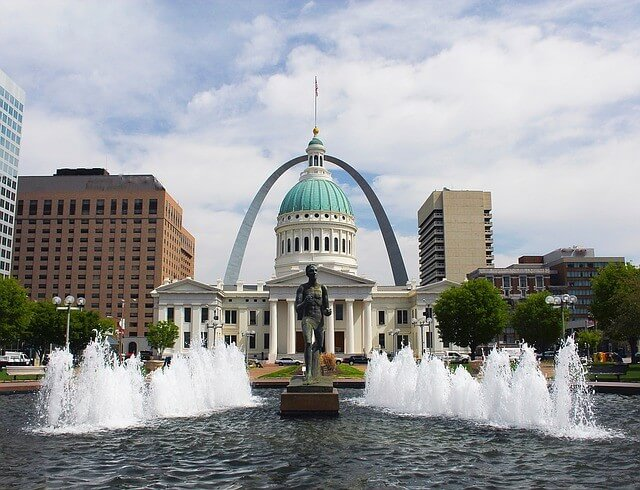 A statue sits in front of a courthouse in downtown St. Louis, Missouri, with the iconic Gateway Arch looming in the background.